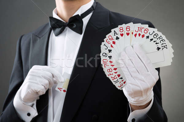Magician Showing Fanned Out Cards Against Gray Background Stock photo © AndreyPopov