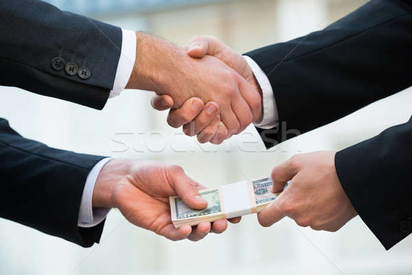 Businessman Shaking Hand While Bribing Partner Stock photo © AndreyPopov