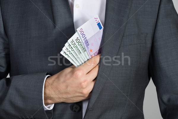 Businessman Putting Bribe In Suit Pocket Stock photo © AndreyPopov