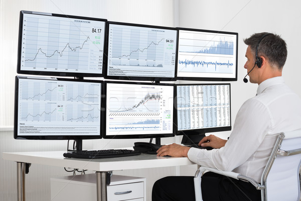 Stock Market Broker Looking At Graphs On Multiple Screens Stock photo © AndreyPopov
