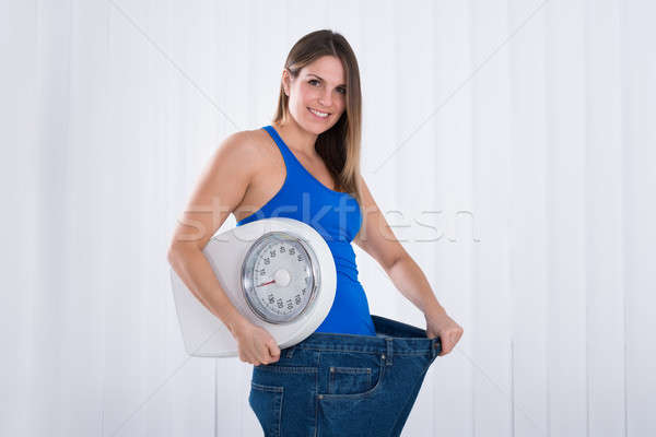 Woman With Weighing Machine Wearing Big Jeans Stock photo © AndreyPopov