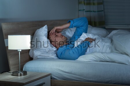 Man Suffering From Headache Lying On Bed Stock photo © AndreyPopov
