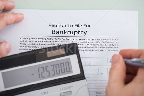 Person Hand And Calculator Over Bankruptcy Form Stock photo © AndreyPopov
