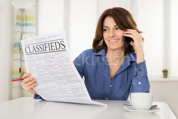 Сток-фото: женщину · газета · говорить · мобильного · телефона · счастливым