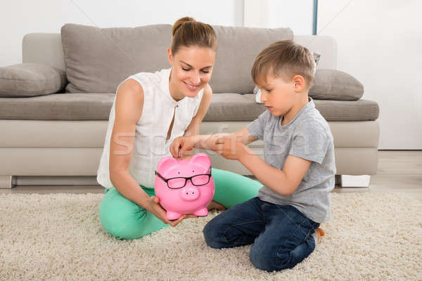 Boy Inserting Coin In Piggybank Stock photo © AndreyPopov