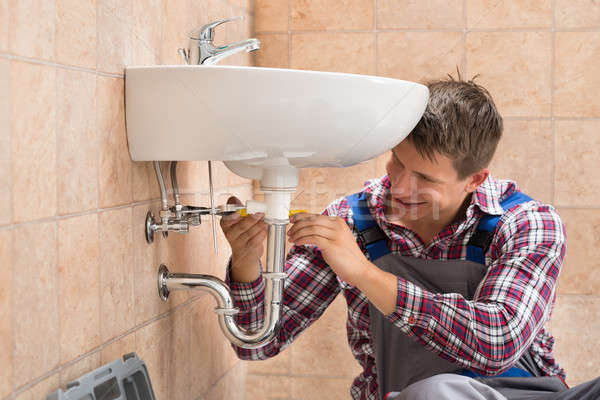 Smiling Plumber Repairing Sink Stock photo © AndreyPopov