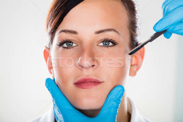 Surgeon's Hand With Scalpel Near Woman's Face Stock photo © AndreyPopov