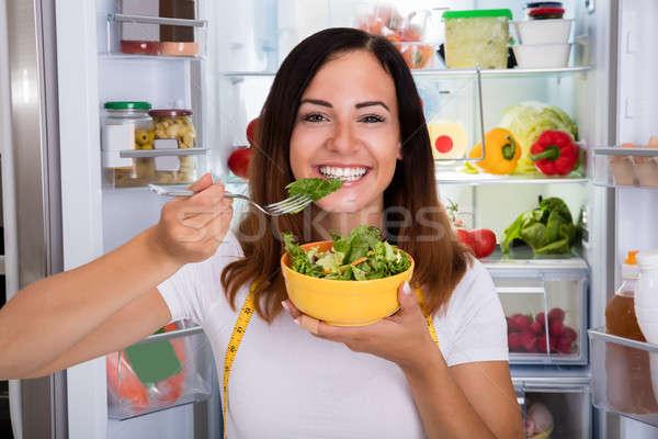Kobieta jedzenie Sałatka lodówce portret uśmiechnięty Zdjęcia stock © AndreyPopov