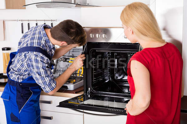 Young Woman Looking At Male Worker Repairing Oven Stock photo © AndreyPopov