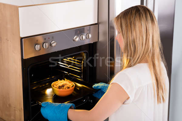 Woman Preparing Food In Oven Stock photo © AndreyPopov