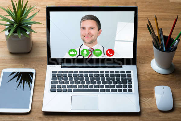 Doctor Smiling While Video Conferencing On Laptop In Hospital Stock photo © AndreyPopov