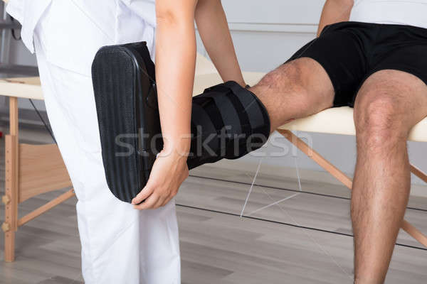 Therapist Fixing Walking Brace On Person's Leg Stock photo © AndreyPopov