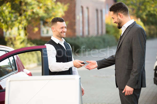 Young Businessman Getting Car Key From Valet Stock photo © AndreyPopov