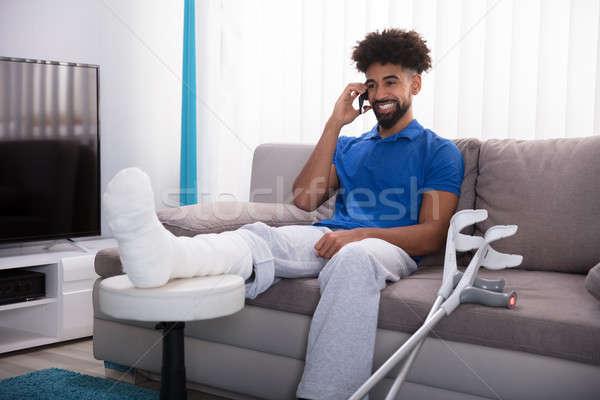 Сток-фото: счастливым · молодым · человеком · сломанной · ногой · говорить · мобильного · телефона · сидят