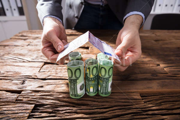 Businessperson Making House Of Banknotes Stock photo © AndreyPopov