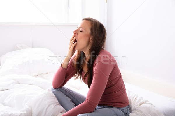 Nő ásít ágy gyönyörű fiatal nő hálószoba Stock fotó © AndreyPopov