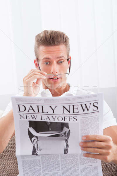 Stock photo: Reading Newspaper With The Headline New Layoffs