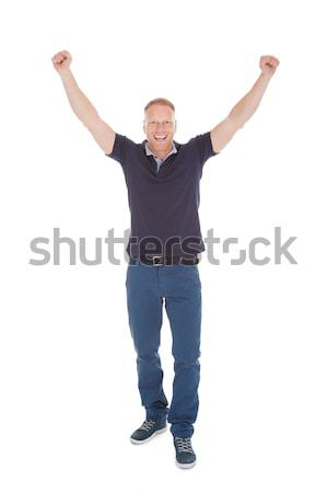 Cheerful Young Man With Hands Raised Stock photo © AndreyPopov