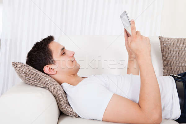 Man Using Digital Tablet While Lying At Home Stock photo © AndreyPopov