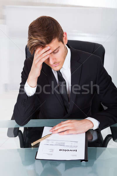 Tired Businessman With Invoice At Desk Stock photo © AndreyPopov