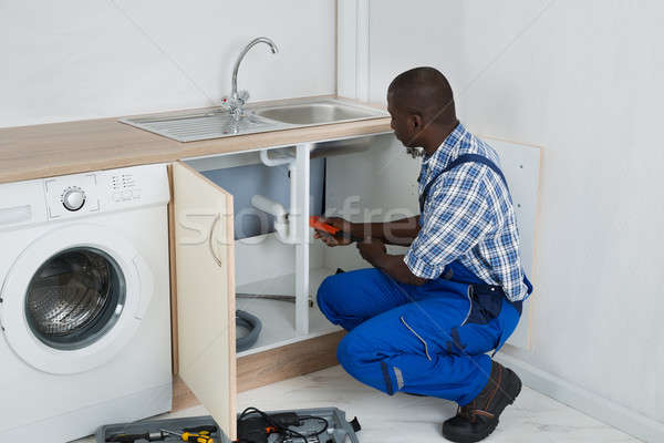 Plumber Fixing Sink In Kitchen Stock photo © AndreyPopov