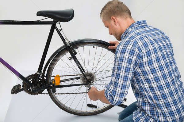 Young Man Repairing Bike Stock photo © AndreyPopov