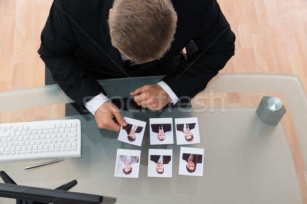 üzletember néz fénykép fiatal asztal iroda Stock fotó © AndreyPopov