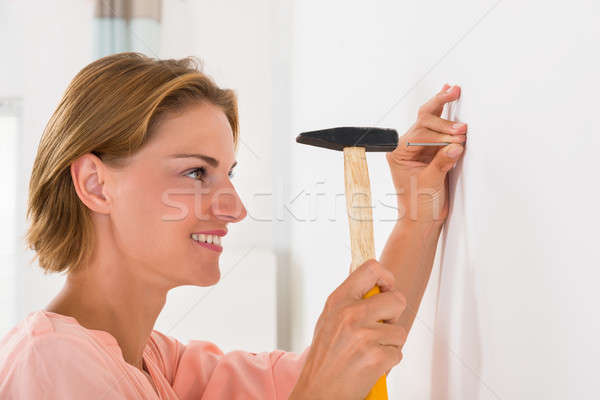 Young Woman Hitting Nail In A Wall Stock photo © AndreyPopov