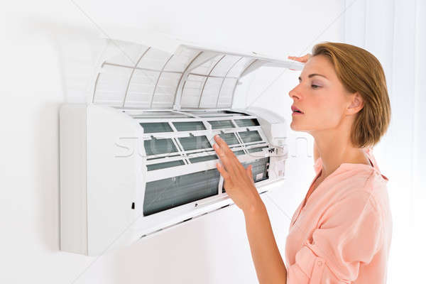 Woman Opening Air Conditioner Stock photo © AndreyPopov