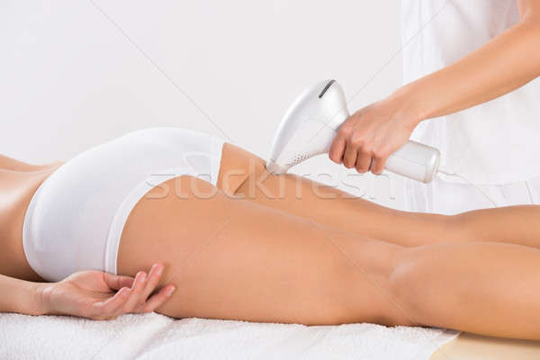 Beautician Using Laser Machine On Young Customer's Leg Stock photo © AndreyPopov