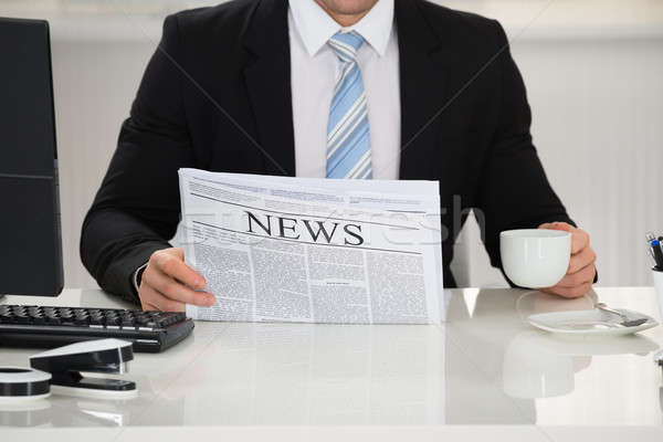 Businessman Holding Newspaper And Coffee Cup At Desk Stock photo © AndreyPopov
