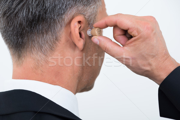 Businessman Inserting Hearing Aid In Ear Stock photo © AndreyPopov