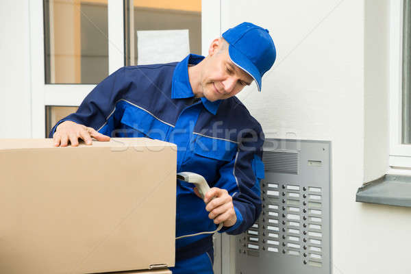 Delivery Man Scanning Cardboard Boxes With Barcode Scanner Stock photo © AndreyPopov