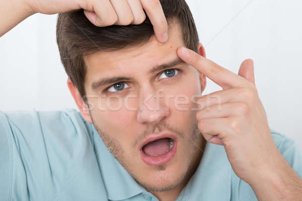 Man Looking At Pimple On Forehead Stock photo © AndreyPopov