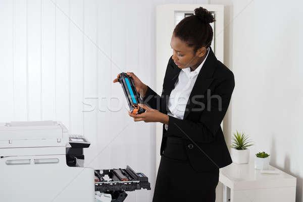 Businesswoman Fixing Cartridge In Office Stock photo © AndreyPopov