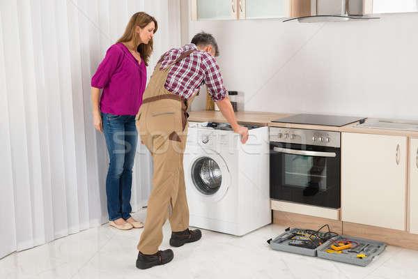 Işçi tamir çamaşır makinesi mutfak olgun kadın bakıyor Stok fotoğraf © AndreyPopov