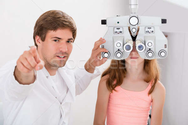 Optometrist Checking Girl's Vision With Phoropter Stock photo © AndreyPopov