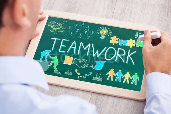 Businessperson Drawing Teamwork Concept On Slate Stock photo © AndreyPopov