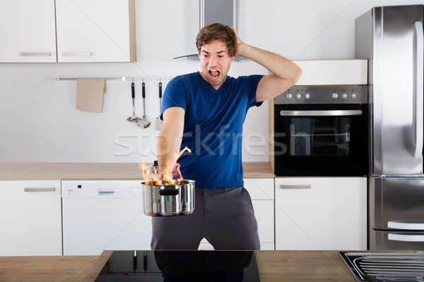 Surprised Man Holding Utensil On Fire Stock photo © AndreyPopov