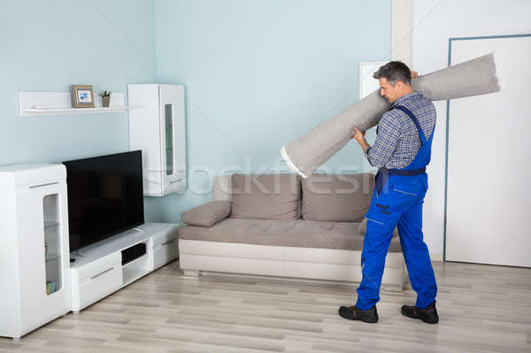 Male Workers Carrying Rolled Carpet Stock photo © AndreyPopov