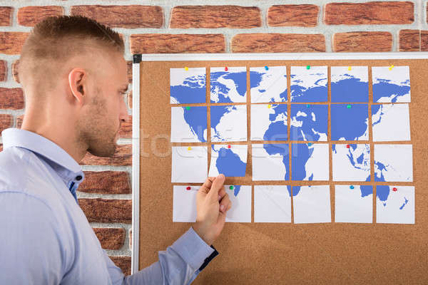 Businessman Looking At World Map Combined From Notes Stock photo © AndreyPopov