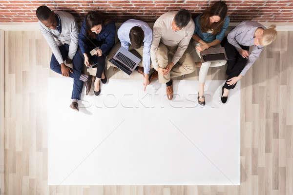 Widoku różnorodny ludzi puste papieru posiedzenia drewnianej podłogi Zdjęcia stock © AndreyPopov