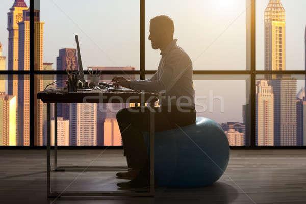 Businessman Sitting On Blue Fitness Ball Stock photo © AndreyPopov