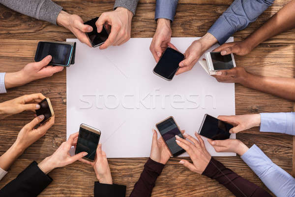 Elevated View Of Businesspeople Hand Using Mobile Phone Stock photo © AndreyPopov