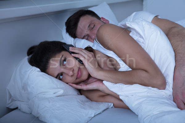 Woman Using Mobile Phone While Husband Sleeping Stock photo © AndreyPopov