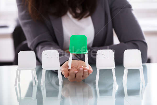 Businesswoman Choosing Green Chair Among White Chairs In A Row Stock photo © AndreyPopov