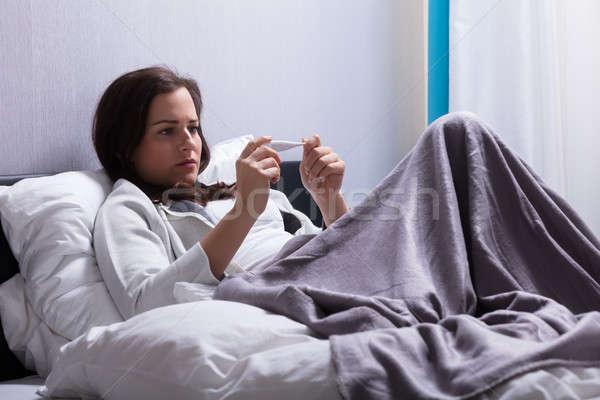 Ziek vrouw lichaam temperatuur thermometer jonge vrouw Stockfoto © AndreyPopov