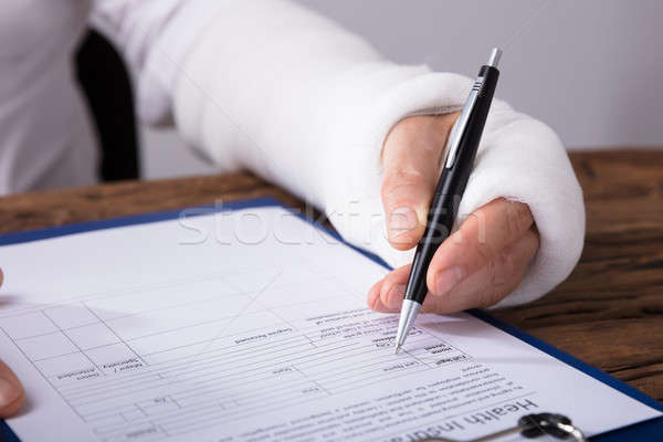 Man With Broken Arm Filling Health Insurance Claim Form Stock photo © AndreyPopov