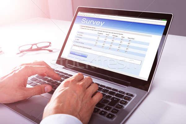 Işadamı doldurma çevrimiçi anket form dizüstü bilgisayar Stok fotoğraf © AndreyPopov