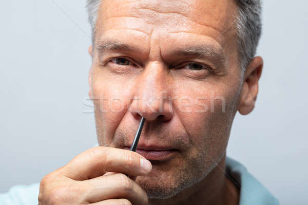 Man Plucking Nose Hair With Tweezers Stock photo © AndreyPopov